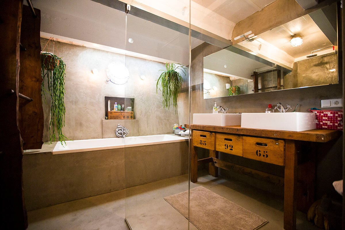 The industrial style bathroom with large bath and sinks.