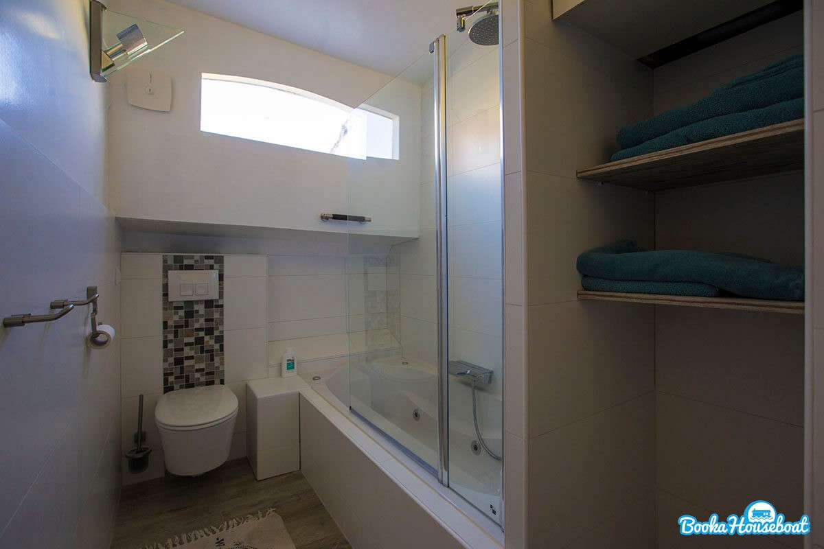The bathroom is equipped with a large bath and shower.