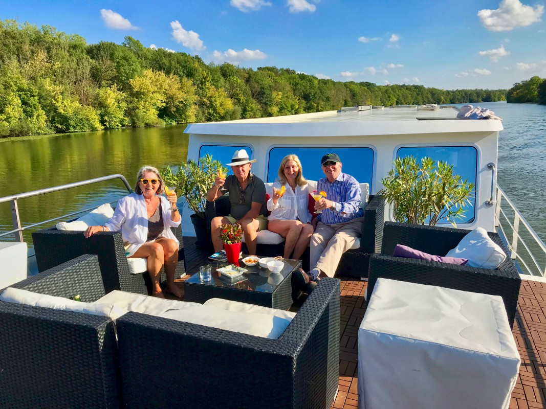 Guests enjoying cocktails on the Grand Victoria while cruising on the River Saône in Burgundy, France