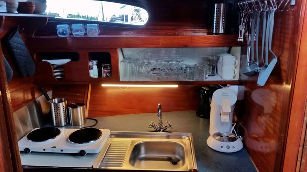 A modest kitchen fully equipped with coffee machine, water cooker, cooking facilities, etc.